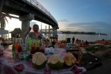 Seorang pedagang menyiapkan minuman berbuka puasa di bawah jembatan Gentala Arasy, tepi Sungai Batanghari, Jambi. Rabu (14/4/2020). Jembatan yang menjadi ikon wisata Provinsi Jambi itu menjadi pilihan sejumlah warga, utamanya kaum muda untuk menunggu waktu berbuka puasa. ANTARA FOTO/Wahdi Septiawan/hp.