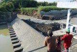 Sejumlah warga melihat tanggul Dam Kedung Banteng yang jebol di Pilangkenceng, Kabupaten Madiun, Jawa Timur, Jumat (16/4/2021). Menurut warga tanggul dam yang memiliki daerah irigasi seluas 654 hektare sawah tersebut jebol sepanjang sekitar 30 meter akibat banjir yang terjadi Rabu (14/4). Antara Jatim/Siswowidodo/zk.