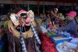 Pedagang menyaksikan tarian Barong Bangkung saat tradisi Ngelawang dalam rangkaian perayaan Hari Raya Galungan di Pasar Desa Adat Mengwi, Badung, Bali, Jumat (16/4/2021). Tradisi yang digelar setiap Hari Raya Galungan dan Kuningan tersebut merupakan ritual tolak bala untuk menetralisir aura negatif dalam merayakan hari kemenangan dharma (kebaikan) melawan adharma (kejahatan). ANTARA FOTO/Nyoman Hendra Wibowo/nym.