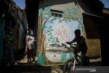 Sejumlah anak bermain di depan mural kaligrafi di Kampung Wisata Budaya Kaligrafi di Bandung, Jawa Barat, Jumat (16/4/2021). Warga di kawasan tersebut berswadaya untuk membuat mural kaligrafi dan menghias tembok dengan potongan hadits, ayat Al Quran hingga Asmaul Husna untuk memberikan susana kampung yang unik namun tetap bernuansa Islami bagi masyarakat sekitar ataupun pendatang. ANTARA JABAR/Novrian Arbi/agr