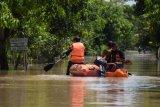 Petugas Badan Penanggulangan Bencana Daerah (BPBD) memantau kondisi banjir di Desa Jerukgulung, Balerejo, Kabupaten Madiun, Jawa Timur, Kamis (15/4/2021). Sejumlah desa di empat kecamatan di Kabupaten Madiun terendam banjir luapan Sungai Jeroan akibat hujan deras Rabu (14/4) sore hingga malam. ANTARA FOTO/Siswowidodo/aww.