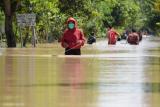 Sejumlah warga menerobos jalan yang terendam banjir di Desa Jerukgulung, Balerejo, Kabupaten Madiun, Jawa Timur, Kamis (15/4/2021). Sejumlah desa di empat kecamatan di Kabupaten Madiun terendam banjir luapan Sungai Jeroan akibat hujan deras Rabu (14/4) sore hingga malam. ANTARA FOTO/Siswowidodo/aww.