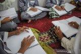 Siswa penyandang disabilitas membaca Al Quran braile saat mengikuti pesantren ramadan di Panti Sosial Rehabilitasi Penyandang Disabilitas Dinsos Jabar, Cimahi, Jawa Barat, Sabtu (17/4/2021). Pesantren Ramadhan  yang diikuti oleh 50 siswa penyandang disabilitas tersebut digelar dalam rangka mengisi waktu luang di bulan suci ramadan untuk memperdalam ilmu agama dengan membaca Al Quran, ibadah dan hafalan doa. ANTARA JABAR/Raisan Al Farisi/agr