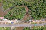 Pekerja menyelesaikan pembangunan Jembatan Peneradan baru di samping Jembatan Peneradan lama, Jalan Lintas Sumatera, Pemayung, Batanghari, Jambi, Jumat (16/4/2021). Balai Pelaksanaan Jalan Nasional (BPJN) Jambi menargetkan penyelesaian pembangunan tujuh jembatan di Kabupaten Batanghari, Merangin, Sarolangun, dan Tanjungjabung Barat pada 2021 guna meningkatkan akses logistik nasional di provinsi itu. ANTARA FOTO/Wahdi Septiawan/aww.