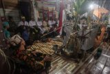 Sejumlah basir (rohaniwan) menyanyikan mantra suci di depan sesaji, Balai Palangka (wahana suci) dan Ancak Mihing (tempat sesaji roh suci) saat prosesi ritual keagamaan umat Hindu Kaharingan Balian Pendeng Sawang Garu Dayak Ngaju di Sekre Peradah, Palangkaraya, Kalimantan Tengah, Sabtu (17/4/2021) malam. Ritual tersebut dilakukan untuk mengesahkan roh suci memasuki para calon basir dan duhung teras sawang (mengikuti meminta berkat) agar mendapatkan gelar serta jalan yang terang untuk direstui dewa Hindu Kaharingan. ANTARA FOTO/Makna Zaezar/nym.