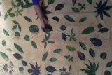 Nanik Riyanti (52), perajin batik yang juga penyandang disabilitas memproduksi batik ecoprint dengan meletakkan aneka daun hijau di atas kain yang telah diberi pewarna dasar di rumah industrinya di Tulungagung, Jawa Timur, Sabtu (17/4/2021). Nanik Riyanto yang mengalami cacat tangan kiri sejak lahir, terus bertahan membatik dengan metode ecoprint kendati harga jualnya mentok di kisaran Rp200 ribu hingga Rp250 ribu per lembar karena keterbatasan pasar. Antara Jatim/Destyan Sujarwoko/zk