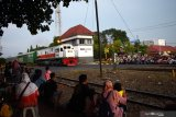 \Sejumlah warga melihat Kereta Api (KA) sambil menunggu saat berbuka puasa atau ngabuburit di sekitar jalur KA dekat kawasan Stasiun KA Madiun, Jawa Timur, Minggu (18/4/2021). Sebagian warga bersama keluarganya memanfaatkan waktu untuk ngabuburit di lokasi itu sambil melihat perjalanan sejumlah KA. Antara Jatim/Siswowidodo/zk