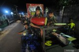 Sejumlah anak-anak memainkan musik perkusi khas Madura berkeliling kampung di Kelurahan Gladak Anyar,  Pamekasan, Jawa Timur, Senin (19/4/2021). Kegiatan yang dilakukan selama bulan Ramadhan itu, dimaksudkan untuk membangunkan warga agar makan sahur. Antara Jatim/Saiful Bahri/zk