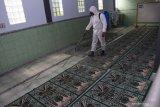 Seorang anggota Polres Madiun menyemprotkan cairan disinfektan di Masjid Baitul Rahman Desa Pagotan, Geger, Kabupaten Madiun, Jawa Timur, Selasa (20/4/2021). Kabupaten Madiun termasuk salah satu daerah yang melakukan perpanjangan Pemberlakuan Pembatasan Kegiatan Masyarakat (PPKM) berbasis Mikro untuk pengendalian penyebaran COVID-19 mulai 20 April hingga 3 Mei 2021. Antara Jatim/Siswowidodo/zk.