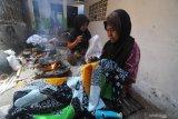 Perajin menyelesaikan pembuatan batik di Desa Klampar, Pamekasan, Jawa Timur, Rabu (21/4/2021). Dibanding bulan lalu produksi batik di daerah itu meningkat sekitar 25 persen atau naik dari 50 potong menjadi 75 potong per perajin dalam satu pekan. Angka tersebut diperkirakan akan terus naik hingga pekan ke tiga Ramadhan tahun ini. Antara Jatim/Saiful Bahri/zk.