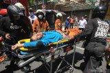 Petugas membawa petugas Dinas Pemadam Kebakaran Kota Surabaya yang mengalami sesak nafas ke rumah sakit saat terjadinya kebakaran rumah di Jalan Genteng Besar, Surabaya, Jawa Timur, Rabu (21/4/2021). Sebanyak 15 kendaraan pemadam kebakaran dikerahkan untuk memadamkan kebakaran rumah yang juga digunakan sebagai gudang tersebut. Dalam kebakaran itu  petugas berhasil mengevakuasi empat orang penghuninya namun salah satunya meninggal dalam perawatan di rumah sakit.  Antara Jatim/Didik Suhartono/zk