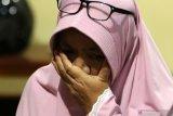 Yayak Dwi Ernawati (46) ibu mertua dari  Serda Pandu Yudha Kusuma awak KRI Nanggala 402 mengusap air mata saat bercerita di rumahnya di Ketapang, Banyuwangi, Jawa Timur, Kamis (22/4/2021). Keluarga awak KRI  Nanggala 402 yang hilang kontak saat menggelar latihan penembakan rudal di laut utara Bali pada rabu (21/4) itu berkumpul menggelar doa bersama agar dalam pencarian tim SAR diberikan kemudahan. Antara Jatim/Budi Candra Setya/zk.