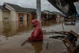 Warga berjalan menembus banjir yang merendam Perumahan Pesona Harapan Indah akibat luapan Sungai Sail di Pekanbaru, Riau, Kamis (22/4/2021). Hujan deras yang mengguyur Kota Pekanbaru mengakibatkan Sungai Sail meluap dan merendam permukiman warga hingga ketinggian air mencapai 1,5 meter di beberapa lokasi sehingga puluhan Kepala Keluarga terpaksa mengungsi sementara ke tempat yang lebih aman. ANTARA FOTO/Rony Muharrman/wsj.