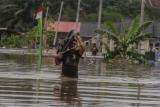 Warga mengevakuasi barang miliknya dari Perumahan Pesona Harapan Indah yang terendam banjir akibat luapan Sungai Sail di Pekanbaru, Riau, Kamis (22/4/2021). Hujan deras yang mengguyur Kota Pekanbaru mengakibatkan Sungai Sail meluap dan merendam permukiman warga hingga ketinggian air mencapai 1,5 meter di beberapa lokasi sehingga puluhan Kepala Keluarga terpaksa mengungsi sementara ke tempat yang lebih aman. ANTARA FOTO/Rony Muharrman/wsj