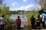 Sejumlah warga menyaksikan danau baru yang muncul dampak dari Siklon Tropis Seroja di Kota Kupang, NTT, Jumat (23/4/2021). Warga setempat menyebut danau dengan luas dua hektare dan dengan kedalaman 40 meter itu sebagai danau Seroja. ANTARA FOTO/Kornelis Kaha/nym
