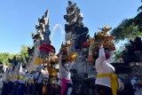 Umat Hindu membawa benda-benda sakral dalam upacara persembahyangan menjelang Hari Raya Kuningan di Pura Sakenan, Denpasar, Bali, Jumat (23/4/2021). Upacara persembahyangan Hari Raya Kuningan yang akan digelar pada Sabtu (24/4/2021) tersebut tetap memperketat penerapan protokol kesehatan dan membatasi jumlah umat ke pura sebagai upaya pencegahan penularan COVID-19. ANTARA FOTO/Nyoman Hendra Wibowo