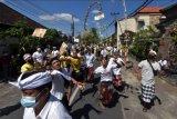 Warga saling berebut menangkap uang yang dilemparkan warga lainnya dalam tradisi Mesuryak di Desa Bongan Gede, Tabanan, Bali, Sabtu (24/4/2021). Tradisi yang bertujuan mengantarkan roh para leluhur kembali ke asalnya dengan rasa suka cita pada Hari Raya Kuningan tersebut digelar dengan durasi singkat yaitu sekitar 5 menit di setiap rumah warga serta membatasi jumlah peserta. ANTARA FOTO/Nyoman Hendra Wibowo/nym.