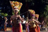 Penari memakai pelindung wajah saat membawakan Tari Rejang Lilit dalam rangkaian Hari Raya Kuningan di Desa Adat Jasri, Karangasem, Bali, Minggu (25/4/2021). Tarian sakral tersebut digelar dengan membatasi jumlah penari yang tampil yakni dari 36 orang menjadi 19 orang untuk mencegah penyebaran COVID-19. ANTARA FOTO/Nyoman Hendra Wibowo/nym.