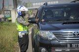 Petugas memeriksa kelengkapan surat dari pengendara dengan nomor polisi luar Bandung di gerbang keluar Tol Cileunyi, Kabupaten Bandung, Jawa Barat, Minggu (25/4/2021). Penyekatan yang dilakukan oleh petugas gabungan dari Kepolisian, Dinas Perhubungan dan Satpol PP tersebut merupakan bagian dari pelaksanaan larangan mudik yang resmi berlaku mulai Sabtu 22 April hingga 24 Mei 2021. ANTARA JABAR/Raisan Al Farisi/agr
