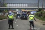 Petugas gabungan memberhentikan kendaraan untuk memeriksa kelengkapan surat dari pengendara dengan kendaraan nomor polisi luar Bandung di gerbang keluar Tol Cileunyi, Kabupaten Bandung, Jawa Barat, Minggu (25/4/2021). Penyekatan yang dilakukan oleh petugas gabungan dari Kepolisian, Dinas Perhubungan dan Satpol PP tersebut merupakan bagian dari pelaksanaan larangan mudik yang resmi berlaku mulai Sabtu 22 April hingga 24 Mei 2021. ANTARA JABAR/Raisan Al Farisi/agr