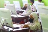 Murid mengerjakan soal PPKn melalui komputer dalam Ujian Sekolah yang diadakan secara tatap muka di SDN Dinoyo 1 Malang, Jawa Timur, Senin (26/4/2021). Ujian sekolah sebagai salah satu syarat kelulusan tersebut diadakan serentak secara tatap muka di 250 sekolah dasar negeri maupun swasta di Kota Malang. Antara Jatim/Ari Bowo Sucipto/zk.
