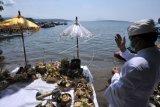 Umat Hindu mengikuti rangkaian ritual Pekelem dan doa bersama di kawasan Labuan Lalang, Buleleng, Bali, Kamis (29/4/2021). Doa-doa yang diikuti personel TNI-Polri bersama masyarakat tersebut dilakukan untuk mendoakan seluruh awak KRI Nanggala 402 yang gugur setelah kapal selam tersebut dipastikan tenggelam di perairan utara Bali serta memohon keselamatan bagi seluruh umat. ANTARA FOTO/Fikri Yusuf/nym.