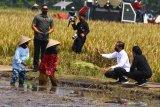 Presiden Joko Widodo (dua dari kanan) didampingi Ketua DPR RI Puan Maharani (kanan) berdialog dengan petani dalam Kunjungan Kerja di Kanigoro, Pagelaran, Malang, Jawa Timur, Kamis (29/4/2021). Dalam kunjungan tersebut, Presiden melakukan panen raya serta memberikan bantuan bagi korban gempa Malang. Antara Jatim/Ari Bowo Sucipto/zk