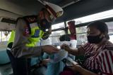 Polisi Lalu Lintas Polres Badung memeriksa kartu identitas penumpang bus saat penyekatan bagi warga yang mudik lebih awal di Badung, Bali, Kamis (29/4/2021). Kegiatan tersebut digelar untuk mengimbau warga agar tidak mudik Lebaran sebagai upaya pencegahan penyebaran COVID-19 dan mengantisipasi terjadinya klaster baru. ANTARA FOTO/Nyoman Hendra Wibowo/wsj.