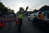 Polisi Lalu Lintas Polres Badung mengatur arus lalu lintas saat penyekatan bagi warga yang mudik lebih awal di Badung, Bali, Kamis (29/4/2021). Kegiatan tersebut digelar untuk mengimbau warga agar tidak mudik Lebaran sebagai upaya pencegahan penyebaran COVID-19 dan mengantisipasi terjadinya klaster baru. ANTARA FOTO/Nyoman Hendra Wibowo/wsj.