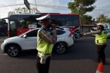 Polisi Lalu Lintas Polres Badung memberikan imbauan kepada pengguna jalan saat penyekatan bagi warga yang mudik lebih awal di Badung, Bali, Kamis (29/4/2021). Kegiatan tersebut digelar untuk mengimbau warga agar tidak mudik Lebaran sebagai upaya pencegahan penyebaran COVID-19 dan mengantisipasi terjadinya klaster baru. ANTARA FOTO/Nyoman Hendra Wibowo/wsj.
