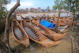 Penjual merapikan beberapa perahu miliknya yang ditambatkan di muara Sungai Tungkal Ilir, Tanjungjabung Barat, Jambi, Kamis (29/4/2021). Perahu yang didatangkan dari Indragiri Hilir, Riau dengan menempuh perjalanan laut selama 24 jam menuju Tanjungjabung Barat itu dijual antara Rp5 juta sampai Rp8 juta per unit. ANTARA FOTO/Wahdi Septiawan/wsj.