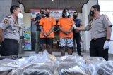 Kepala Badan Narkotika Nasional (BNN) Provinsi Bali Brigjen Pol Gde Sugianyar Dwi Putra (kanan) menunjukkan tersangka berinisial YE (ketiga kiri) dan RP (ketiga kanan) beserta barang bukti kasus narkotika jenis ganja di Kantor BNN Kabupaten Badung, Bali, Senin (3/5/2021). Petugas BNNK Badung berhasil menangkap tersangka YE dan RP beserta barang bukti ganja seberat 9,1 kilogram yang dikirim dari daerah Sumatera Utara melalui jasa ekspedisi dan dimasukkan ke dalam bungkusan karung pakaian bekas. ANTARA FOTO/Fikri Yusuf/nym.