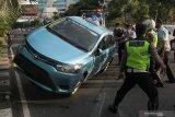 Petugas bahu-membahu membalikkan taksi Bluebird yang terbalik di Jalan A Yani, Surabaya, Jawa Timur, Senin (3/5/2021). Taxi Bluebird yang bernomor lambung WE 832 dengan nomor polisi L 1732 UO tersebut diduga mengalami kecelakaan tunggal saat melintas di jalan tersebut dan pengemudinya dilarikan ke rumah sakit untuk menjalani perawatan. Antara Jatim/Didik Suhartono/zk.