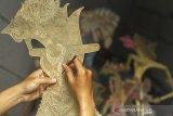 Perajin menyelesaikan pembuatan kerajinan wayang kulit di workshop Panurat Jagat, Desa Banyuasih, Banyusari, Karawang, Jawa Barat, Senin (3/5/2021). Kerajinan wayang kulit yang dibuat dari bahan dasar kulit kerbau dan kulit sapi tersebut dijual dengan harga Rp500 ribu - Rp3 juta tergantung bahan kulit, karakter dan tingkat kesulitan. ANTARA JABAR/M Ibnu Chazar/agr