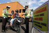 Polisi memeriksa dokumen perjalanan warga dari Pulau Bali yang masuk ke Pulau Jawa di Pelabuhan Ketapang Banyuwangi, Jawa Timur, Minggu (2/5/2021). Pemeriksaan itu dilakukan sebagai pengetatan pergerakan warga jelang masa larangan mudik pada 6-17 mei 2021 sebagai upaya pencegahan penyebaran COVID-19. Antara Jatim/Budi Candra Setya/zk