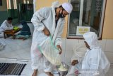 Panitia menimbang beras dari warga saat pembayaran zakat fitrah di Masjid Al Wasilah, Kampung Cinta Rasa, Kota Tasikmalaya, Jawa Barat, Selasa (4/5/2021). Panitia pengumpulan zakat fitrah di masjid tersebut menerima pembayaran zakat fitrah oleh warga sambil menggunakan Alat Pelindung Diri (APD) COVID-19 untuk mensosialisasikan tentang pentingnya protokol kesehatan. ANTARA JABAR/Adeng Bustomi/agr