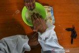 Warga menunaikan pembayaran zakat fitrah di Masjid Al Wasilah, Kampung Cinta Rasa, Kota Tasikmalaya, Jawa Barat, Selasa (4/5/2021). Panitia pengumpulan zakat fitrah di masjid tersebut menerima pembayaran zakat fitrah oleh warga sambil menggunakan Alat Pelindung Diri (APD) COVID-19 untuk mensosialisasikan tentang pentingnya protokol kesehatan. ANTARA JABAR/Adeng Bustomi/agr