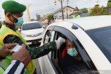 Petugas kesehatan TNI memeriksa suhu tubuh pengendara saat penyekatan dalam rangka larangan mudik di Kota Madiun, Jawa Timur, Selasa (4/5/2021). Penyekatan yang dilakukan petugas gabungan TNI, Polri, Satpol PP dan Badan Penanggulanan Bencana Daerah (BPBD) itu dimaksudkan untuk mengantisipasi pemudik masuk wilayah Kota Madiun guna mencegah penularan COVID-19. Antara Jatim/Siswowidodo/zk