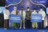 Group Head XL Axiata Region East, Dodik Ariyanto (ke tiga kiri) Staf Khusus Kemenkopolhukam, Rizal Mustary (ke empat kiri) dan Imam Marsudi (kanan) menyerahkan donasi laptop kepada perwakilan pondok pesantren di Pesantren As-Sayuti, Pamekasan,  Jawa Timur, Selasa (4/5/2021). XL Axiata memberikan 100 unit laptop  kepada 12 pondok pesantren di sejumlah daerah,  empat di antaranya berada di Jawa Timur. Donasi ini merupakan bagian dari program Desa Digital yang diinisiasi XL Axiata. Menkopolhukam Mahfud MD bersama Presiden Direktur & CEO XL Axiata Dian Siswarini menyaksikan secara daring  penyerahan donasi tersebut.  Antara Jatim/Saiful Bahri/zk