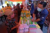 Pedagang melayani warga yang berbelanja saat pasar murah menjelang Hari Raya Idul Fitri 1442 Hijriah di Denpasar, Bali, Selasa (4/5/2021). Kegiatan yang digelar oleh Pemerintah Kota Denpasar pada 4-7 Mei 2021 tersebut untuk meringankan beban ekonomi masyarakat dalam memperoleh bahan pokok dengan harga yang lebih murah dari harga di pasaran. ANTARA FOTO/Nyoman Hendra Wibowo/nym.