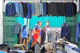Calon pembeli memilih pakaian impor bekas yang dijual di Pasar Angso Duo Baru, Jambi, Sabtu (1/5/2021). Pedagang berharap, penjualan barang impor bekas yang sempat mengalami penurunan hingga 70 persen lebih selama pandemi COVID-19 tersebut bisa membaik mendekati Lebaran tahun ini. ANTARA FOTO/Wahdi Septiawan/rwa.