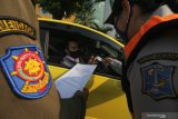 Polisi memeriksa dokumen milik pengendara mobil saat hari pertama penyekatan larangan mudik di Bundaran Waru, Surabaya, Jawa Timur, Kamis (6/5/2021). Penyekatan di sejumlah lokasi perbatasan kota Surabaya dilakukan serentak saat penerapan larangan mudik Lebaran 2021 sebagai upaya pencegahan penularan COVID-19. Antara Jatim/Didik Suhartono/zk