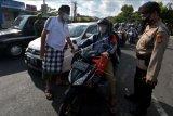 Polisi dibantu pecalang atau petugas keamanan desa adat menghentikan pengendara sepeda motor saat penyekatan larangan mudik di Denpasar, Bali, Kamis (6/5/2021). Kegiatan penyekatan larangan mudik Hari Raya Idul Fitri 1442 Hijriah di Posko Induk Uma Anyar, Denpasar tersebut melibatkan pecalang untuk memperketat pengamanan di jalur itu guna mengantisipasi warga yang nekat pulang kampung. ANTARA FOTO/Nyoman Hendra Wibowo/nym.