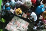 Guru memberikan beras kemasan kepada anak yatim saat penyaluran zakat fitrah di SDN Lawangan Daya 2, Pamekasan,  Jawa Timur, Kamis (6/5/2021). Sekitar 400 paket  beras kemasan dan zakat mal dari siswa sekolah itu, disalurkan kepada anak yatim dan warga tidak mampu di lingkungan sekolah tersebut. Antara Jatim/Saiful Bahri/zk