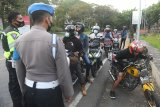 Polisi menghentikan pengendara motor yang hendak menyeberang ke Jawa karena tidak melengkapi diri dengan surat izin khusus saat dimulainya penyekatan mudik Lebaran di Pos Penyekatan kawasan Cekik, Pelabuhan Gilimanuk, Bali, Kamis (6/5/2021). Petugas gabungan mulai menyekat jalur mudik sejak Kamis (6/5) pukul 00.00 Wita dan penyeberangan Gilimanuk-Ketapang ditutup bagi pemudik hingga 17 Mei 2021 dalam upaya mencegah penyebaran COVID-19. ANTARA FOTO/Nyoman Budhiana.