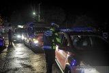 Petugas memeriksa kelengkapan surat dari pengendara yang memiliki kendaraan dengan plat nomor luar Garut di perbatasan Kabupaten Bandung dan Kabupaten Garut, Kadungora, Kabupaten Garut, Jawa Barat, Rabu (5/5/2021) malam. Pada H-1 larangan mudik lebaran 2021, petugas Kepolisian di posko penyekatan Kadungora membalikan arah 30 kendaraan yang akan mudik ke arah jalur selatan Garut-Tasikmalaya. ANTARA JABAR/Raisan Al Farisi/agr