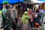 PENGAWASAN PUSAT KERAMAIAN JELANG LEBARAN. Personel gabungan Polri, TNI dan Satpol PP memberikan masker gratis kepada seorang pedagang saat pengawasan pusat keramaian di Pasar Aceh, Banda Aceh, Aceh, Kamis (6/5/2021). Polda Aceh mengintensifkan pengawasan menjelang Idul Fitri di sejumlah pusat keramaian untuk penegakan disiplin protokol kesehatan dan selain imbauan agar warga mengenakan masker dan menjaga jarak  guna mencegah penyebaran COVID-19. ANTARA FOTO/Ampelsa.