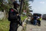 Petugas kepolisian bersenjata lengkap berjaga di jalur Gerbang Tol Karawang Barat saat penyekatan larangan mudik di Karawang, Jawa Barat, Jumat (7/5/2021). Pengetatan penjagaan dalam penyekatan akses transportasi menuju gerbang tol tersebut sebagai upaya antisipasi kendaraan yang nekat mudik menerobos jalur penyekatan. ANTARA JABAR/M Ibnu Chazar/agr