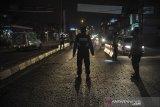 Petugas kepolisian memberhentikan kendaraan di posko penyekatan perbatasan Kabupaten Bandung dan Kabupaten Sumedang di Jatinangor, Kabupaten Sumedang, Jawa Barat, Jumat (7/5/2021). Pada H+2 larangan mudik lebaran 2021, posko penyekatan Jatinangor memutarbalikkan sebanyak 149 roda empat, dan 102 roda dua. ANTARA JABAR/Raisan Al Farisi/agr