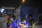 Petugas kepolisian memeriksa sebuah truk di posko penyekatan perbatasan Kabupaten Bandung dan Kabupaten Sumedang di Jatinangor, Kabupaten Sumedang, Jawa Barat, Jumat (7/5/2021). Pada H+2 larangan mudik lebaran 2021, posko penyekatan Jatinangor memutarbalikkan sebanyak 149 roda empat, dan 102 roda dua. ANTARA JABAR/Raisan Al Farisi/agr